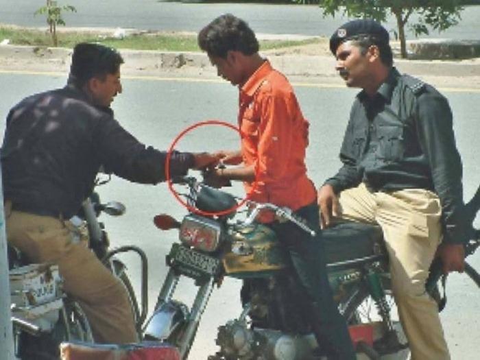 police officer taking money from a man on motor bike