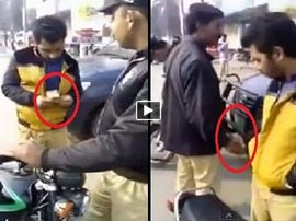 Police officer caught taking bribe from a man on motor bike